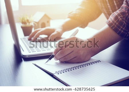Left-hand manager putting his ideas and writing business plan at workplace,man holding pens and papers, making notes in documents, on the table in office,vintage color,morning light ,selective focus. #628735625