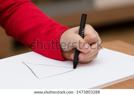 Left hand of a child drawing on white paper using black crayon #1473803288