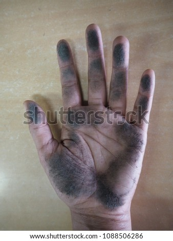 Left hand of Thai woman dirty because it touches black dust on wooden table. #1088506286