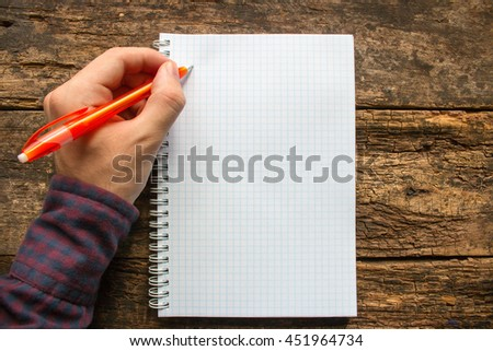 left-handed man writes in a notebook