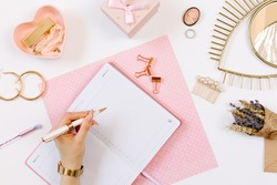 Left-hander girl keeps a diary and planning a day on stylish workplace. Female hand write in pink notebook. Women blog concept with pink notebook and golden watch. Flat lay style.