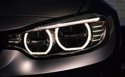 Left headlight by night. Car detail. The front lights of the metalic blue lux sports car. Car's light. New led front light by night. The front lights of the car, in hybrid sports car