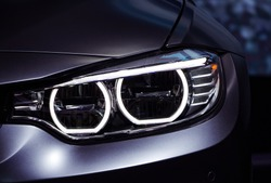 Left headlight by night. Car detail. The front lights of the metallic blue lux sports car. Modern Car's light.