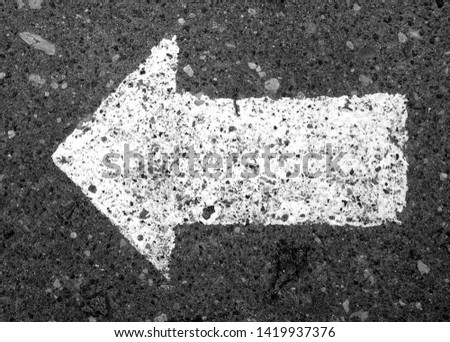 Left pointing arrow on asphalt in black and white. Signs and symbols. #1419937376
