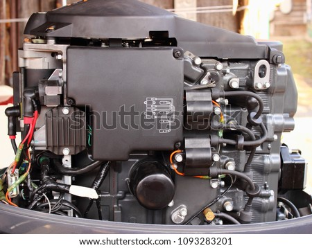 Left side of four-stroke outboard motor with electric starter and ignition coils #1093283201