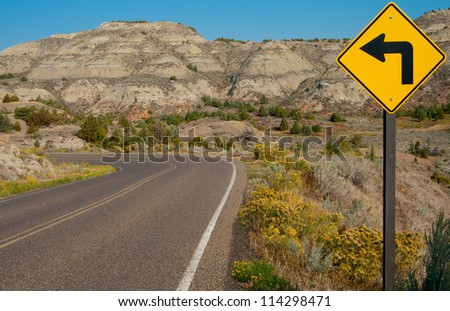 Left Turn Sign:  A road sign warns of a sharp left turn on a narrow road through Theodore Roosevelt National Park in southwest North Dakota.
