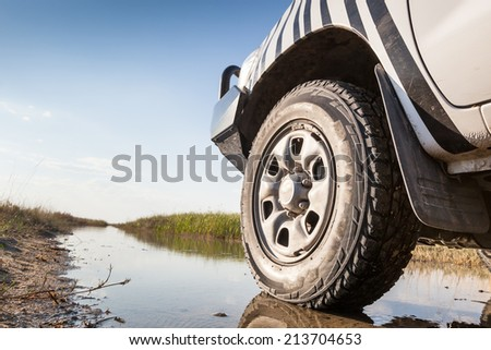 left wheel of a white 4x4 car on a wet trail in the marsh of Nata bird sanctuary, Botswana, Africa Stock photo ©