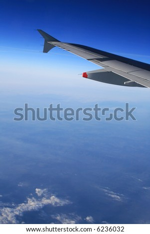 Left wing of the aircraft in the air over clear sky above and some clouds below. Free space for text below the wing.