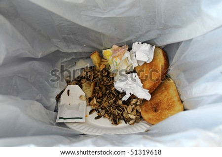 Leftover food and trash in a garbage bin