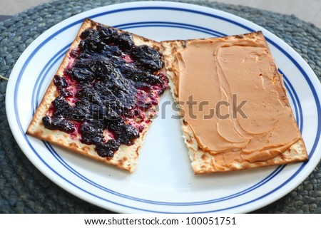 Leftover Matzohs. Two pieces of after Passover matzohs covered in peanut butter & jelly arranged on white porcelain plate. - stock photo
