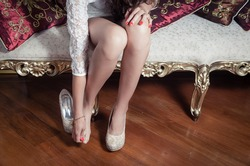 leg caption of model girl wearing white dress sitting on victorian sofa with one shoe on left foot and holding other hand over right toes