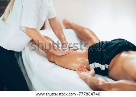 Leg massage. Physical therapyst massaging leg of young male athelete