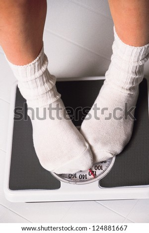 Leg of a woman standing on a bathroom scale