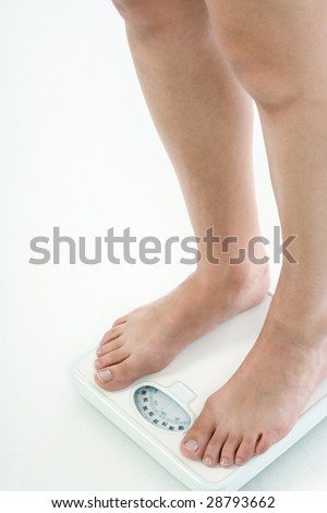 Leg of Caucasian female with untidy nails standing on bathroom scales, checking her weight over 220 lbs