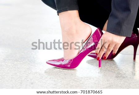 leg of woman beauty put on pink high heels hand holding woman has ankle pain from her high heels. #701870665