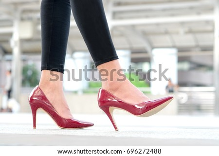 leg of woman beauty put on red high heels Walk on the street #696272488