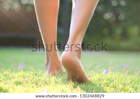 Leg of woman is on walk down the grass to exercise in the morning. Health and Relaxation Concepts