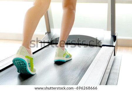 leg of woman running on treadmill in the gym which runner athletic by running shoes. Health and sport concept background,  Healthy lifestyles