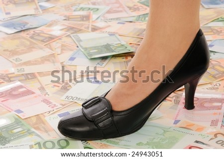 Leg on banknotes (money under control - concept) - stock photo