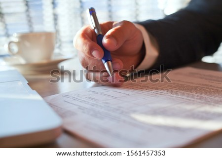 legal advice from lawyer or notary, compliance, verification of contract conditions,  close up of hand with pen and document