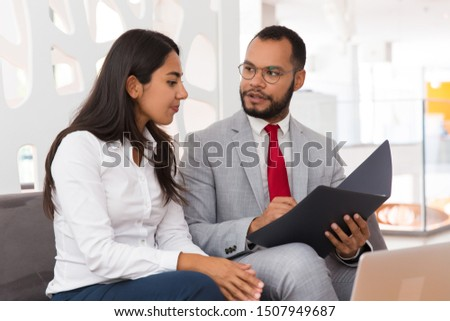 Legal expert explaining document specifics to customer. Business man and woman sitting on office couch with open folder and discussing papers. Expertise concept #1507949687