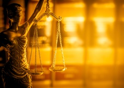 Legal law concept image, scales of justice lit by golden light.