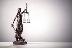 Legal law concept statue of Lady Justice with scales of justice background