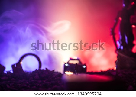 Legal law or crime concept. Man alone standing in the middle of the road on a foggy night. Artwork decoration with handcuffs, Statue of Justice and mallet of justice on toned foggy background.