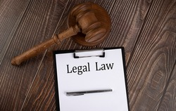 LEGAL LAW text on paper with gavel on the wooden background