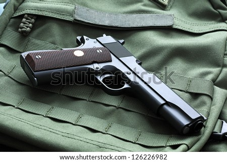 "Legendary semi-automatic M1911 Mark IV Series 80 .45 caliber pistol on a green background with the ""U.S. Army"" patch. Studio shot."