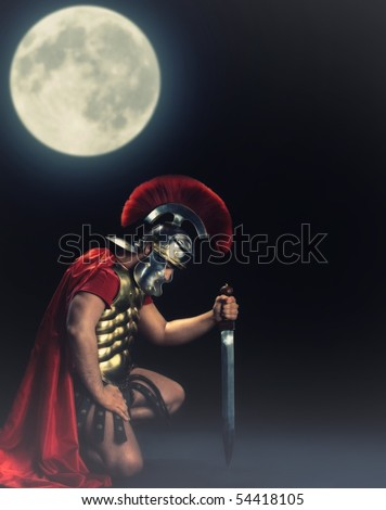 Legionary soldier standing on a knee at night time - stock photo