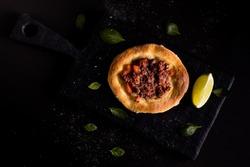Legitimate Arabic sfiha meat on black cutting board and lemon cut in half on black background