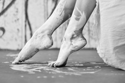 Legs and feet of a Young artistically abstract painted woman ballerina with white paint. Creative body art, art, painting.