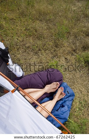 Legs and feet of couple sticking out of tent