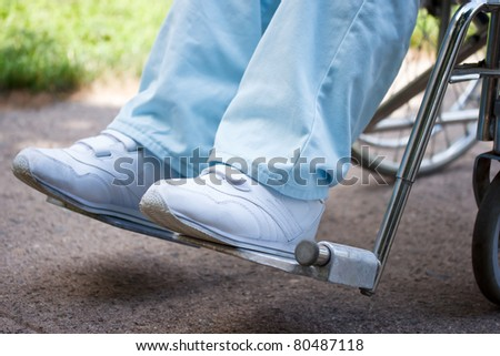 Legs and feet of woman sitting in wheelchair