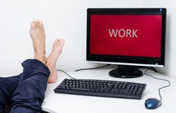 legs and feet without shoes on desk with red screen