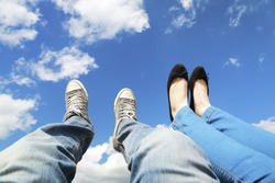 legs dangling in the blue sky with clouds