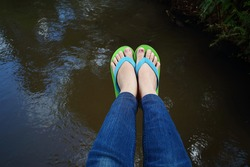 legs dangling on the river