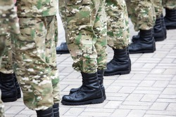 Legs in black military boots. Conscription into the army.