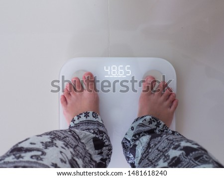 legs in casual wearing stand on weight scale ,result display on screen in Kg.