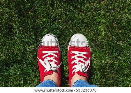 Legs in old red sneakers on green grass. View from above. The concept of youth, spring and freedom. #633236378