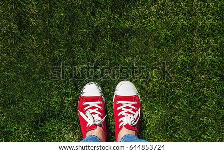 Legs in old red sneakers on green grass. View from above. The concept of youth, spring and freedom. #644853724