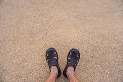 Legs in sneakers on sandstone floor, terrazzo floor, gravel floor.