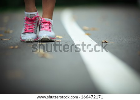 Legs in sneakers on the track