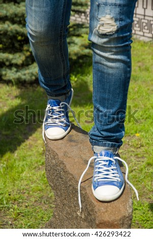 Legs in sports shoes and ripped jeans on the stone/ Legs in ripped jeans on the stone/ The laces have come undone on both shoes #426293422