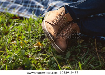 legs in yellow leather boots on lush green grass #1058919437