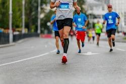 legs man runner in black compression socks run under rain drops on road in city