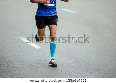 133bebd06 legs man runner in blue compression socks running on asphalt road
