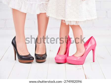legs mother and daughter little girl fashionista in pink shoes on high heels
