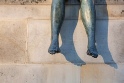 legs of a bronze sitting statue in front of beige stone background; they cast a thick shadow because of low evening sun